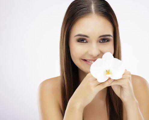 Branhaariges Model lächelt und hält die Blüte einer Orchidee am Kinn.