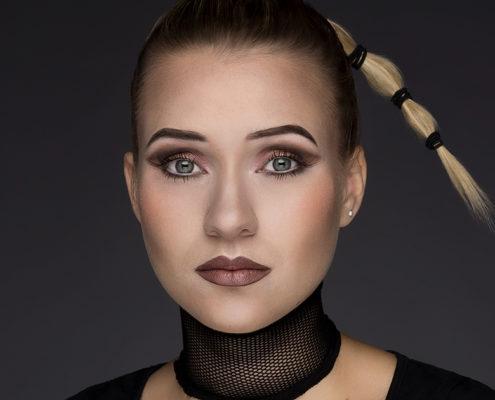 Junge Frau mit frechem, blondem Zopf vor dunkelgrauem Hintergrund. Sie trägt auffälliges Make-Up mit schwarzem Halsband.